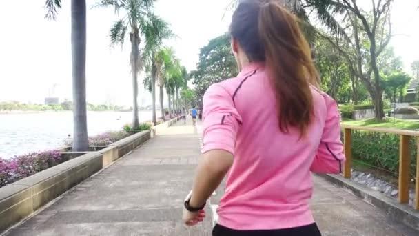 Slow motion - mladé Asijské žena běží na chodníku v ráno. Asijské žena mladý sport běh v parku. Fitness sportovní lidé a koncept zdravého životního stylu.