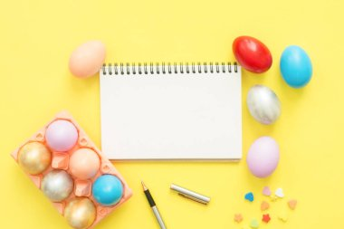Flat lay top view colorful easter egg painted in pastel colors composition and mock up blank notebook with paint brush on yellow pastel color background. Easter day background top view with copy space