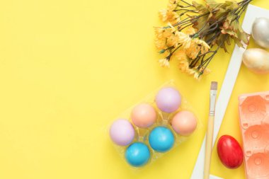 Flat lay top view colorful easter egg painted in pastel colors composition and spring flowers with paint brush on yellow pastel color background. Easter day background top view with copy space.