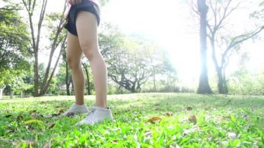 Slow motion - Healthy asian woman exercising at park. Fit young woman doing training workout in morning. Young happy asian woman stretching at park after a running workout. Exercise outdoor concept.