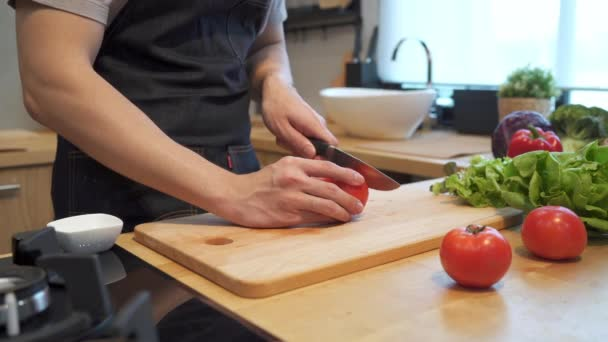 Asian man hands cutting tomato on chopping board. Close up shot of fresh vegetables on kitchen counter. Male is preparing food in kitchen at home.