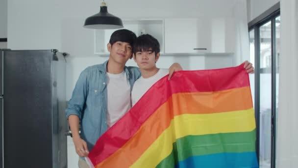 Porträt eines jungen asiatischen schwulen Paares, das sich glücklich fühlt, zu Hause die Regenbogenfahne zu zeigen. asien lgbtq + männer entspannen zahmes lächeln mit blick in die kamera, während sie sich morgens in der modernen küche im haus umarmen.
