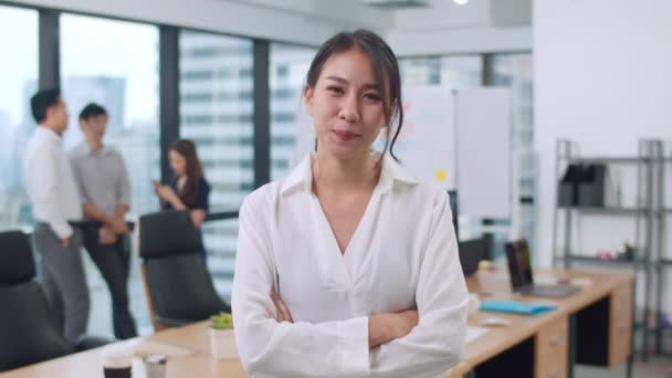 Portrét úspěšné krásné výkonné podnikatelky chytré ležérní oblečení při pohledu do kamery a úsměvu, ruce zkřížené na moderním kancelářském pracovišti. Mladá asijská dáma stojící v moderní zasedací místnosti.