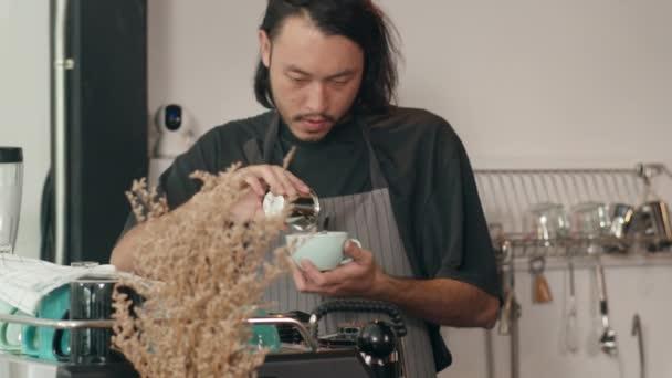 Zamyšlený mladý asijský barista pracující s kávovarem v kavárně. Malý podnikatel korejský muž v zástěře a černé tričko s kávou u kávovaru u pultu v městské kavárně.