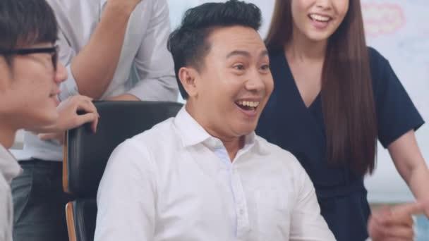 Millennial Gruppe junger Geschäftsleute Asiens Geschäftsmann und Geschäftsfrau feiern das Schenken von fünf, nachdem sie sich glücklich fühlen und einen Vertrag oder eine Vereinbarung in einem Besprechungsraum in einem kleinen modernen Büro unterzeichnen.