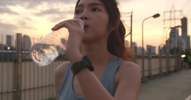 Beautiful young Asia athlete lady exercises drinking water because feel tired after running in urban environment. Japanese teen girl work out wearing sports clothes on walkway bridge in early morning.
