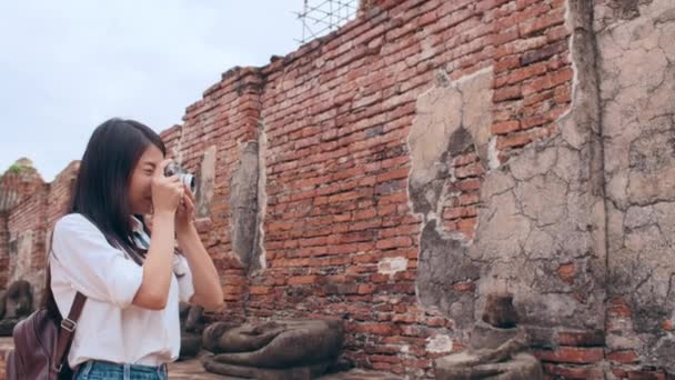 Traveler Asian woman using camera for take a picture while spending holiday trip at Ayutthaya, Thailand, Japanese female tourist enjoy her journey at amazing landmark in traditional city. Slow motion.