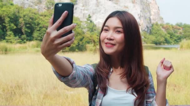 Cheerful young traveler Asian lady with backpack recording video vlog live streaming on phone upload in social media at mountain lake. Korean girl happy enjoy holiday trip. Lifestyle travel and relax.