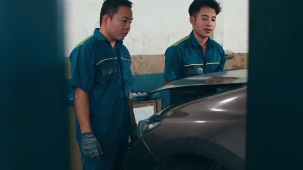 Dva profesionální automechanici šroubují detaily automobilového motoru na zdvižený automobil na opravárenských čerpacích stanicích. Dovedný Asiat v uniformě opravuje auto v noci v garáži. Koncept autoservisu. Zpomalený pohyb.