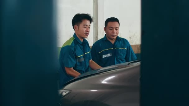 Two professional car mechanic screwing details of car engine on lifted automobile at repair service station. Skillful Asian guy in uniform fixing car at garage night. Car service concept. Slow motion.