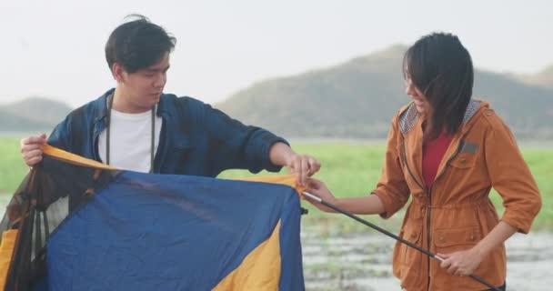Mladé asijské táborníci pár nastavení stan camping zařízení venku u moře. Mužské a ženské cestování baví v letní den v kempu. Venkovní aktivity, dobrodružství cestování, nebo dovolená.