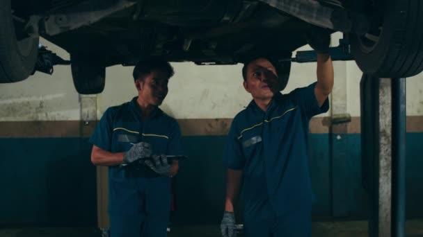 Dva profesionální automechanik pomocí papírování dělá olej a motor kontrolu k vozu na zvednutý automobil na opravárenských čerpacích stanicích v noci. Šikovný Asiat v uniformě opravující auto. Zpomalený pohyb.