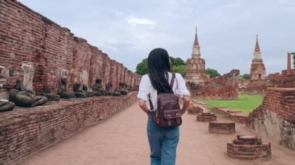 Traveler Asian woman spending holiday trip at Ayutthaya, Thailand, Japanese backpacker female enjoy her journey at amazing landmark in traditional city. Lifestyle women travel holidays concept.