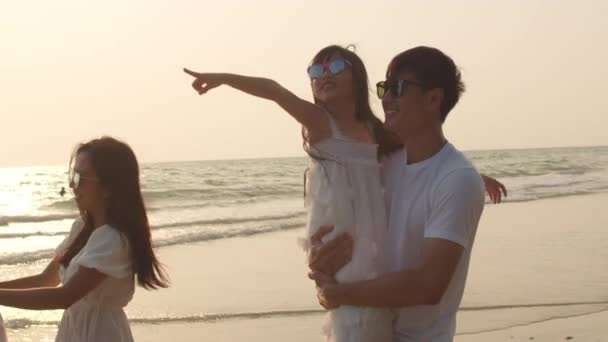 Asian young happy family enjoy vacation on beach in evening. Dad, mom and kid relax walking together near sea when sunset. Lifestyle travel holiday vacation summer trip concept. 4k slow motion.