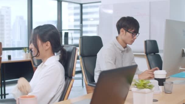 Multikulturális üzletemberek együttműködő folyamatcsoportja intelligens alkalmi viseletben kommunikál és használja a technológiát, miközben együtt dolgoznak a kreatív irodában. Ázsia csapat fiatal szakemberek dolgoznak.