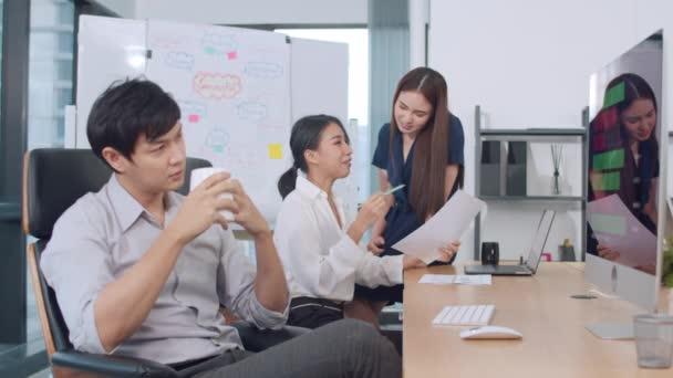 Spolupracující procesní skupina multikulturních podnikatelů v inteligentních příležitostných oděvech při práci v kreativní kanceláři komunikuje a používá technologie. Asijský tým mladých profesionálů pracovat.