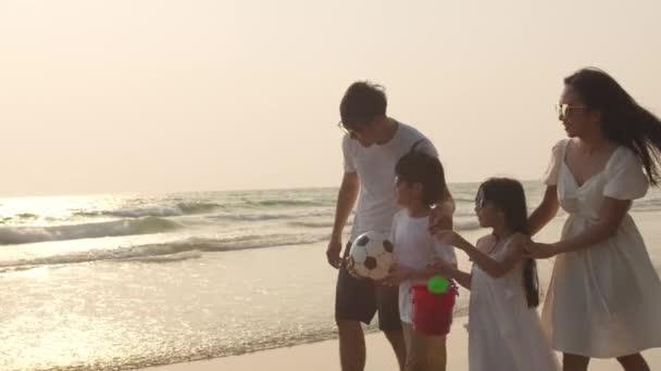 Asijské mladé šťastný rodina těšit dovolenou na pláži ve večerních hodinách. Tati, máma a děcko se při západu slunce společně procházejí u moře. Životní styl cestování dovolená dovolená letní výlet koncept. 4k zpomalený pohyb.
