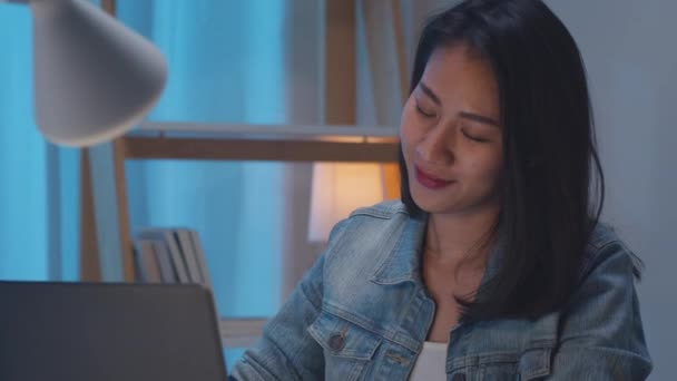 Zeitlupe - Freelance smart business women listening music after use laptop work hard in living room at home night. Glückliche junge asiatische Mädchen sitzen auf Schreibtisch Überstunden, Tanz genießen entspannen Zeit.