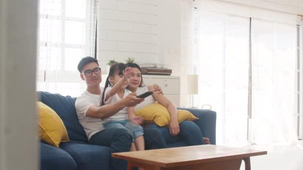 Glückliche asiatische Familien genießen ihre Freizeit entspannt zu Hause. Lifestyle Koreanisch papa, mutter und tochter fernsehen zusammen und haben spaß liegend auf sofa im wohnzimmer im modernen haus.