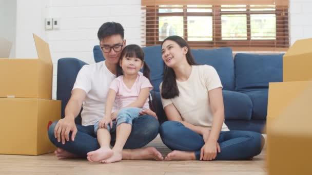 Šťastní asijští majitelé domů si koupili nový dům. Korejská máma, táta a dcera se těší na budoucnost v novém domově poté, co se přestěhovali do relokace a seděli spolu na podlaze s krabicemi.