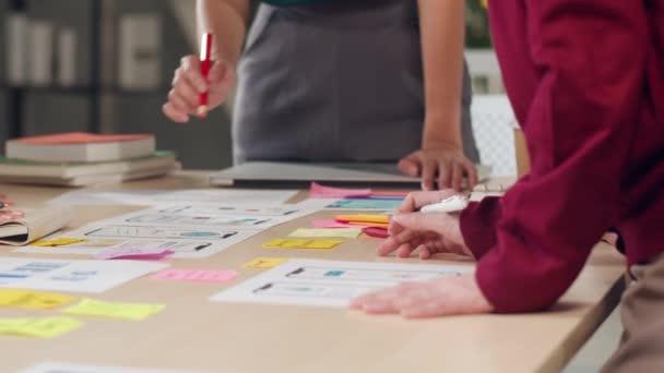 Asiatische Geschäftsleute und Geschäftsfrauen treffen sich zu Brainstorming-Ideen über kreative Web-Design-Plananwendung und entwickeln Vorlagen-Layout für Mobiltelefon-Projekte, die im Büro zusammenarbeiten. Zeitlupe.