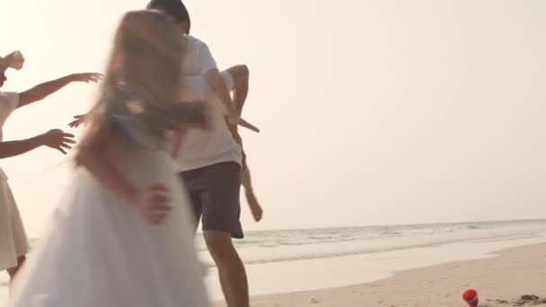 Asian young happy family enjoy vacation on beach in the evening. Dad, mom and kid relax playing together near sea when sunset. Lifestyle travel holiday vacation summer trip concept. 4k slow motion.
