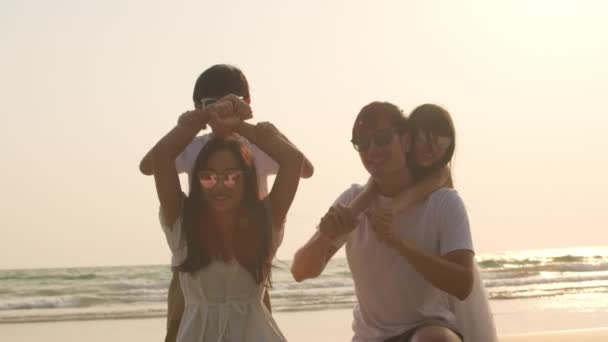 Asian young happy family enjoy vacation on beach in evening. Dad, mom and kid set camera for take photo while relax together near sea when sunset. Lifestyle travel holiday vacation summer. Slow motion