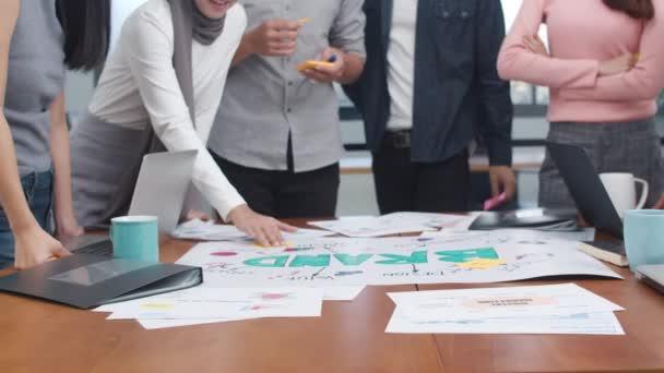 Detailní záběry šťastných mladých asijských podnikatelů, kteří se setkávají s myšlenkami na nové kolegy z administrativních projektů, kteří společně plánují úspěšnou strategii, si užívají týmové práce v úřadu. Zpomalený pohyb.