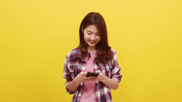Smiling adorable Asian female using phone with positive expression, smiles broadly, dressed in casual clothing and looking at camera over yellow background. Happy adorable glad woman rejoices success.