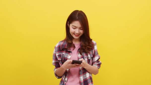 Mosolygó imádnivaló ázsiai nő telefonnal pozitív kifejezéssel, széles mosollyal, alkalmi ruhába öltözve, és a kamerát sárga háttérrel. Boldog imádnivaló boldog nő örül a sikernek.