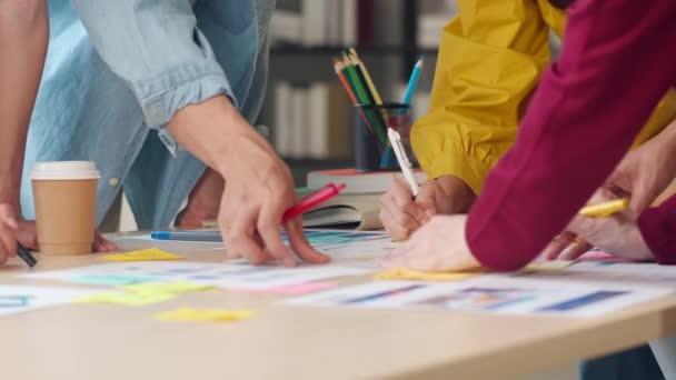 Ázsiai üzletemberek és üzletasszonyok találkoznak ötletbörze ötleteket kreatív web design alkalmazás és dolgozzon sablon elrendezése mobiltelefon projekt dolgozik együtt az irodában. Lassú mozgás..