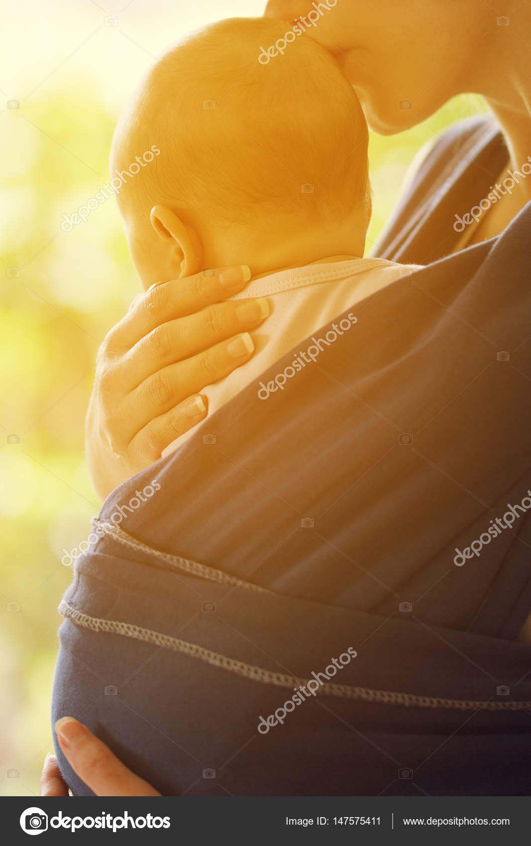 Mother kisses baby seating in sling, closeup. Daylight. — Stock ...