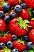 Fotografie Closeup Macro of Tasty Ripe Red Strawberry with Fresh Blue Berries