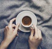 Fotografie Žena ruce držící chutné espresso káva v malém šálku na šedý přehoz