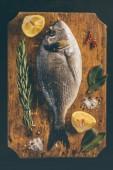 dorado fish with lemon and rosemary at cutting board