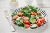 deska s mixem salátových listů a zeleniny a sypané sýrem a granátové jablko semena