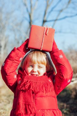 Little girl with gift box in nature