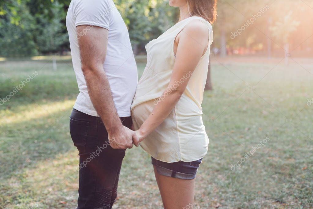 Pregnant couple holding hands and looking at each other in park at sunny day