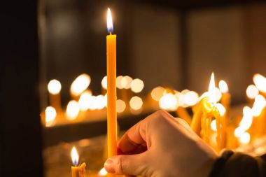 hand holding candle in front of defocused candle flames