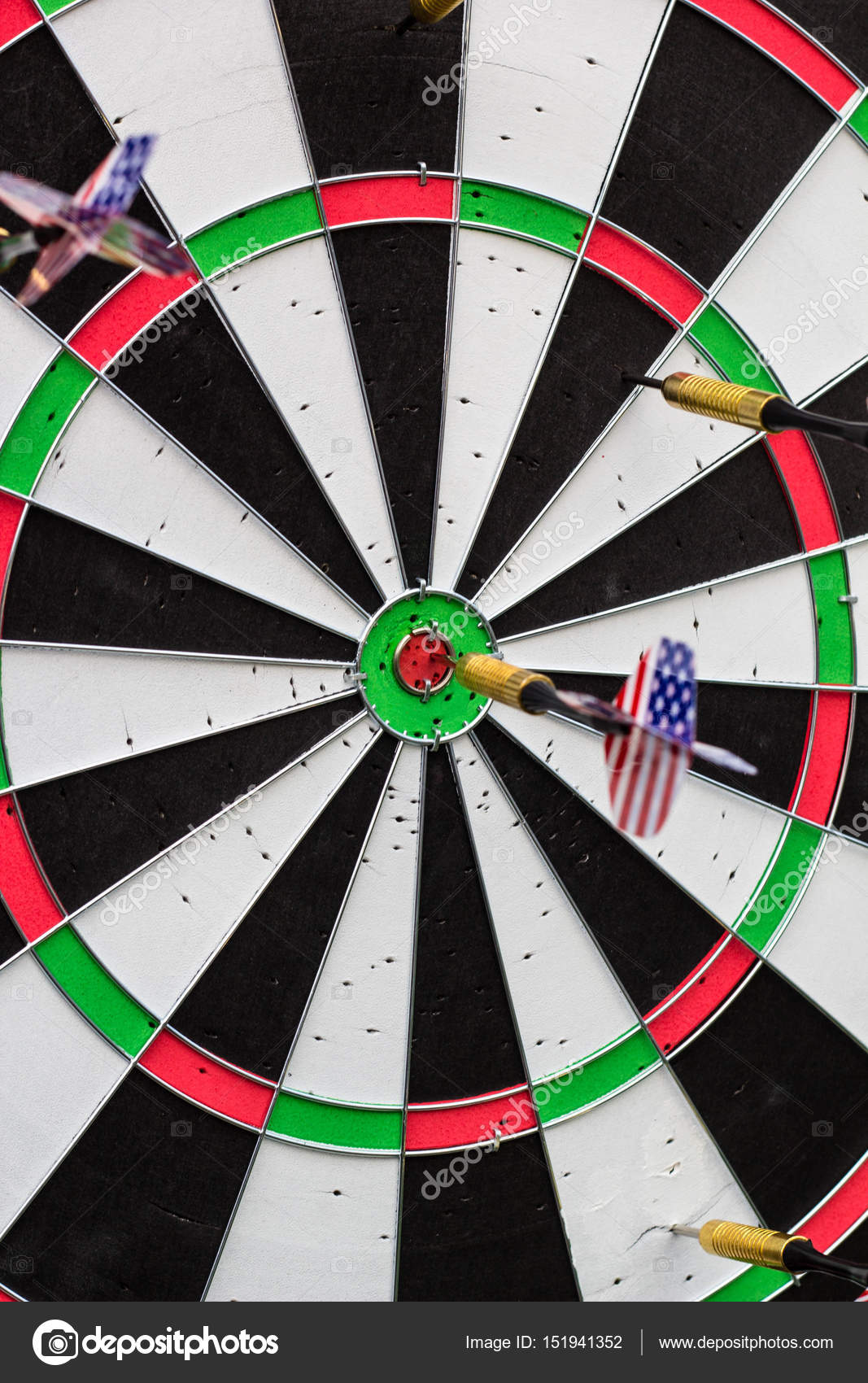 dart in bullseye on the target with many other darts stock photo