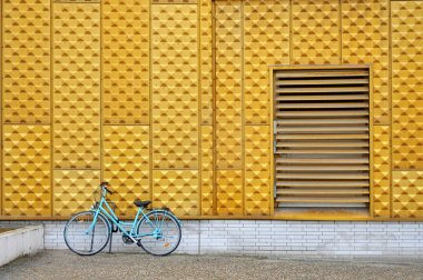 Blue bicycle near yellow wall