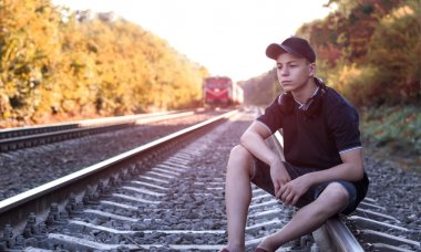 Teenager with headphones listens to music on the railway tracks