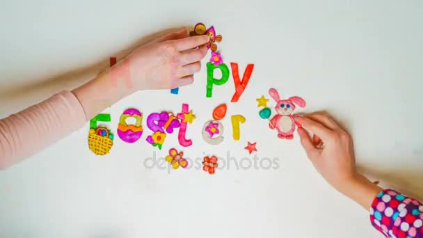 Children make holiday inscription from plasticine and confetti Happy Easter, a motion stop