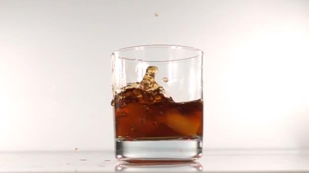 Eis fällt in ein Glas Wasser Zeitlupe