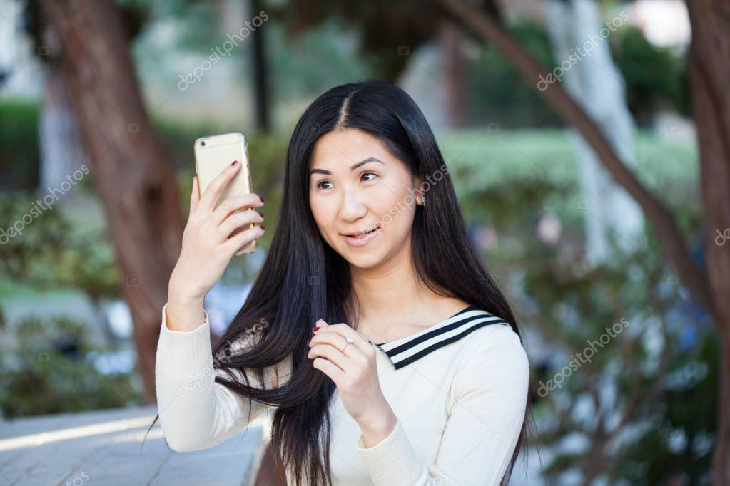 Cute young Asian woman in a beautiful park using her phone.