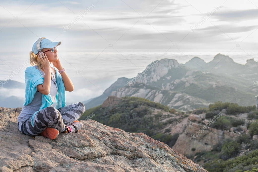 Listening to your soul: beautiful relaxed girl sitting on the mountain summit with her headset on