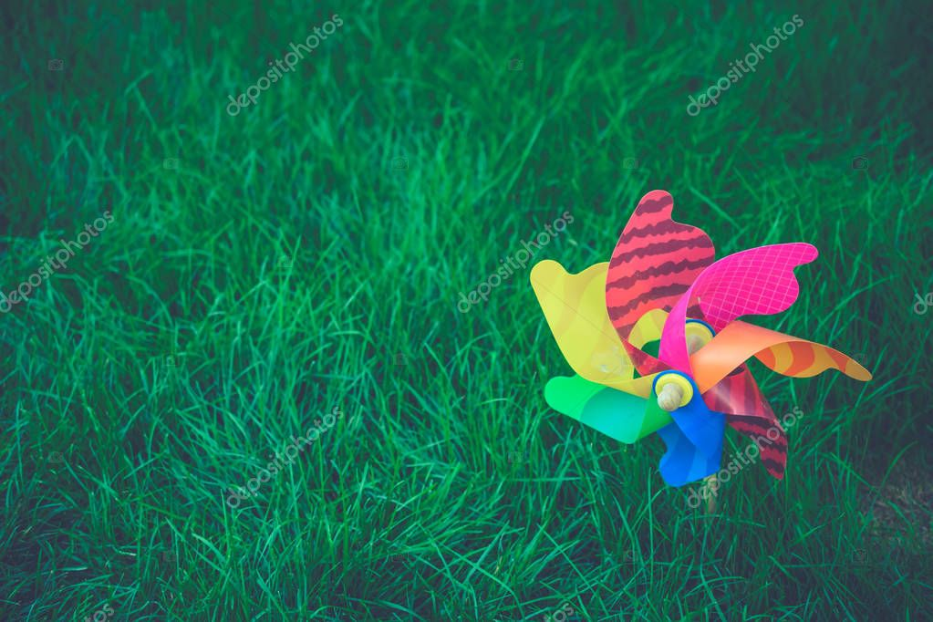 Colorful wind wheels on green grass with blank space, Colorful
