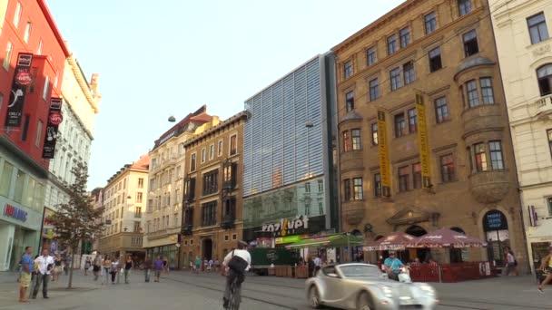 Luxusní auto prochází lidé města Brno, náměstí Svobody,