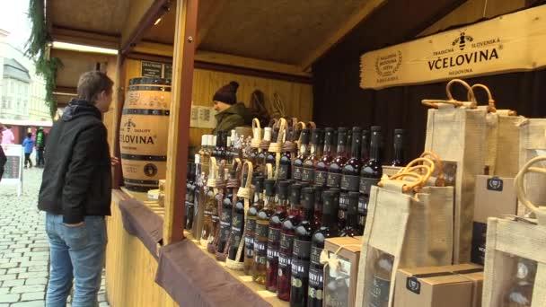 Člověk si koupí původní alkoholický nápoj medoviny na vánoční trhu. Krásné skleněné láhve, vysokou kvalitu a chuť sladkého medu
