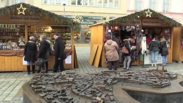 Olomouc, Česká republika, 17 prosince 2017: Lidé na adventním vánočním trhu stání na náměstí, bylinných čajů, pletené rukavice, křesťanské svátky lidi chodící, miniaturní bronzový model města Olomouc, Evropa, Evropská unie